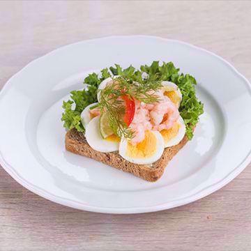 Smørbrød med ferskt brød, sprø salat, nykokt egg, gode reker,  majones og karse. Matspecialen. Påsmurt. Danske Smørbrød. Foto.